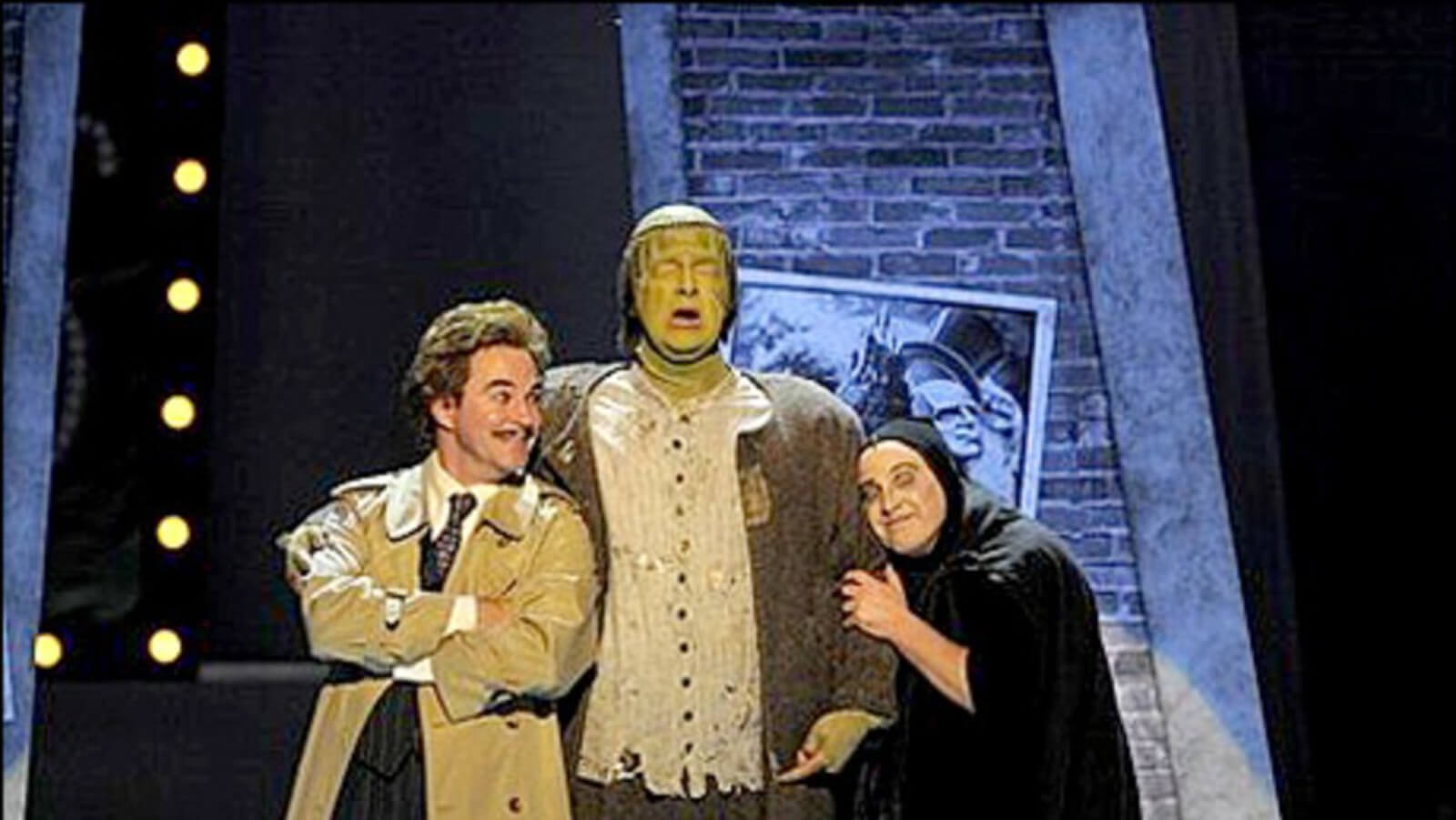 Roger Bart, Shuler Hensley, and Cory English in a scene from Young Frankenstein. Shuler is costumed as the monster and the other gents are leaning in towards him.