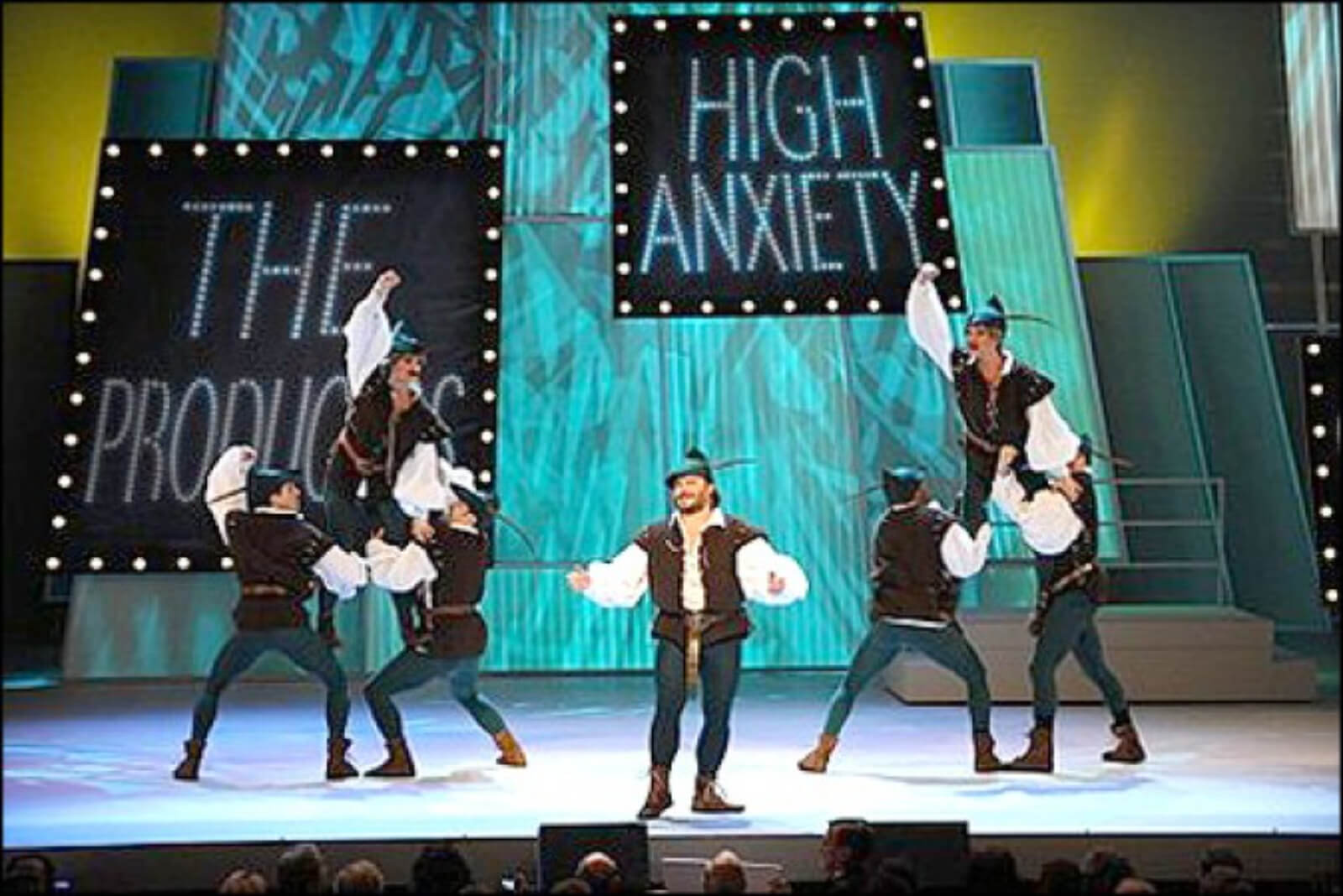 Jack Black and six male dancers - all dressed as Robin Hood, with two men lifted to his left and right with fists in the air.