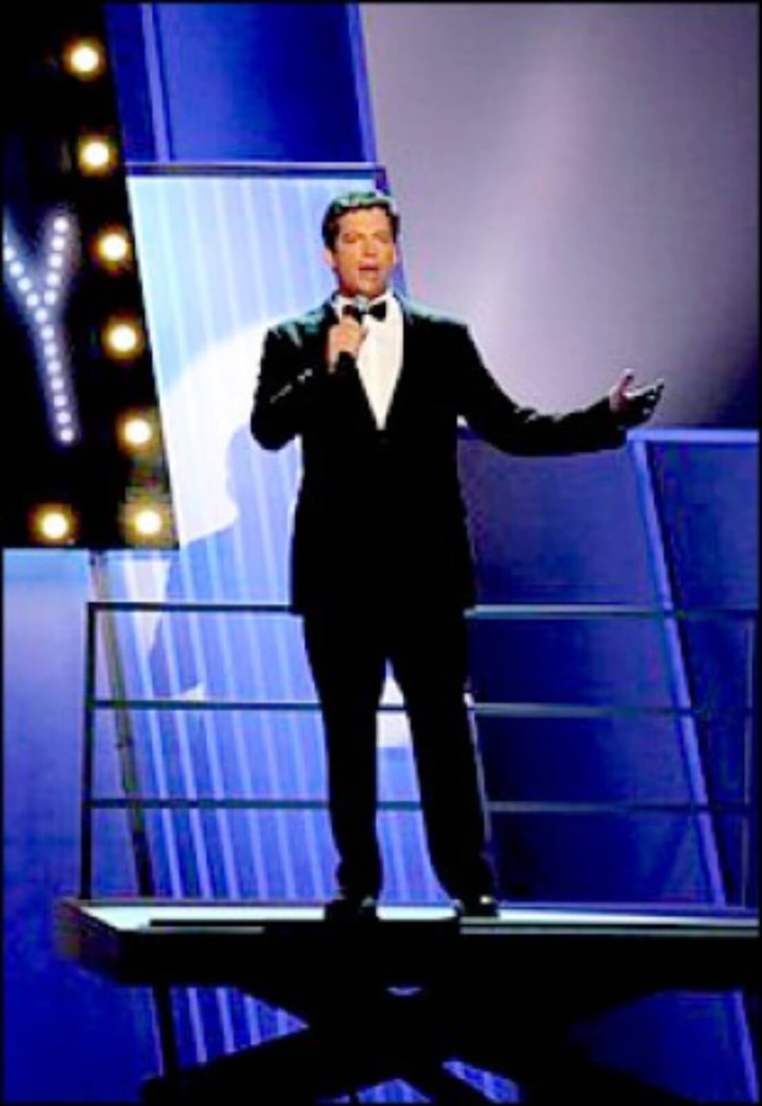 """Harry Connick Jr. singing """"High Anxiety"""" in a black tie and tux with a microphone."""