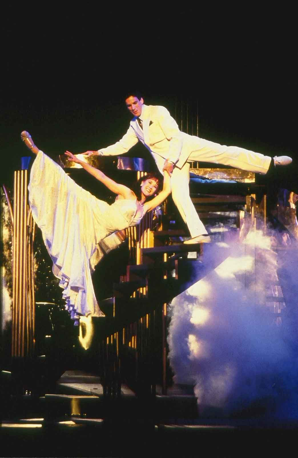 Karen Ziemba and Jimmy Brennan in the finale of Crazy for You. Both dancing on a staircase, in elegant white costumes, and with a leg behind them in arabesque.