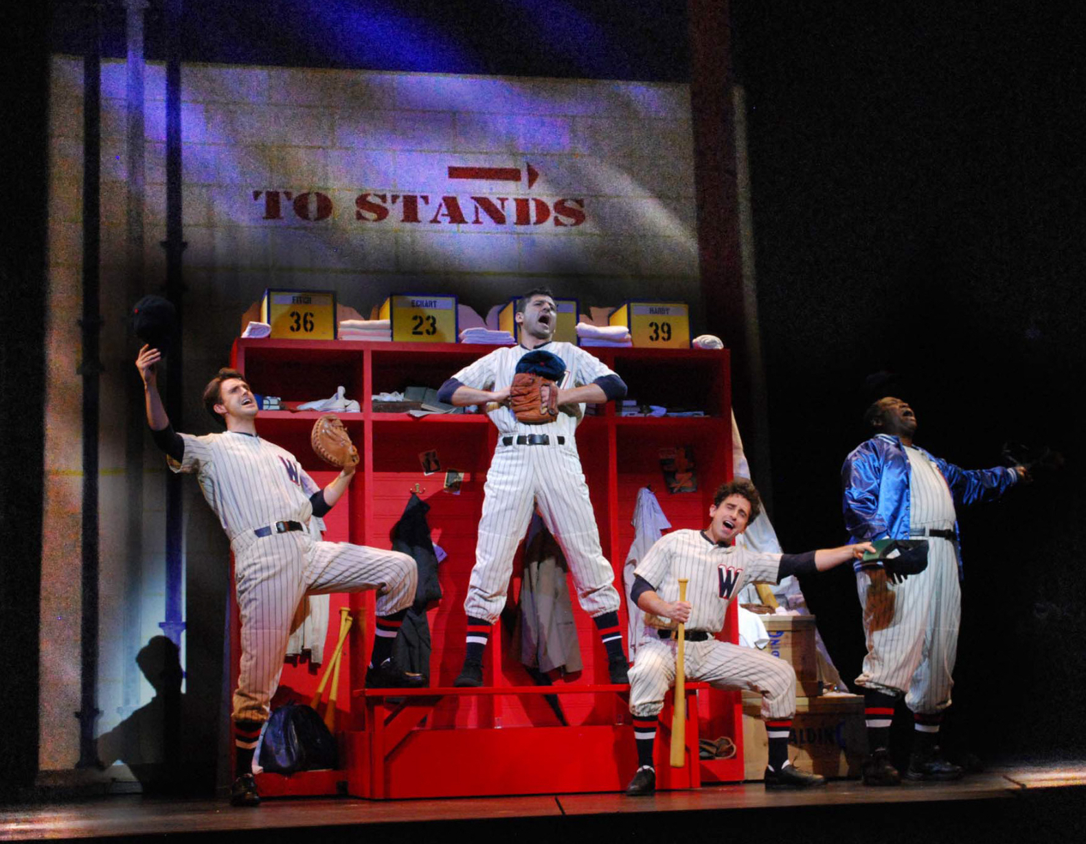 """Michael Xavier, Tony Yazbeck, Brandon Uranowitz and Chuck Cooper sing """"You've Gotta Have Heart"""" from Damn Yankees. They are in a baseball locker room dressed in baseball uniforms joyfully singing in Prince of Broadway."""