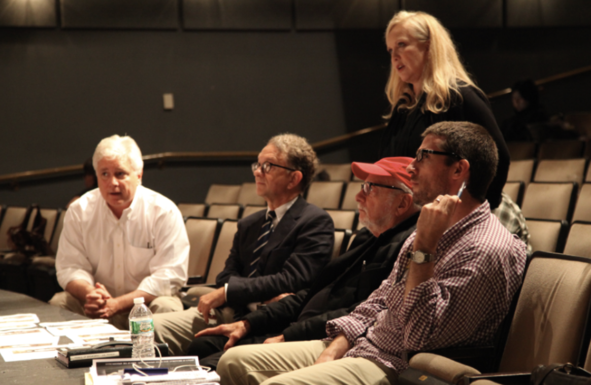 The show's creatives in rehearsal, four of them sitting in the front seats of an empty theatre. Susan Stroman is directing the cast on stage.