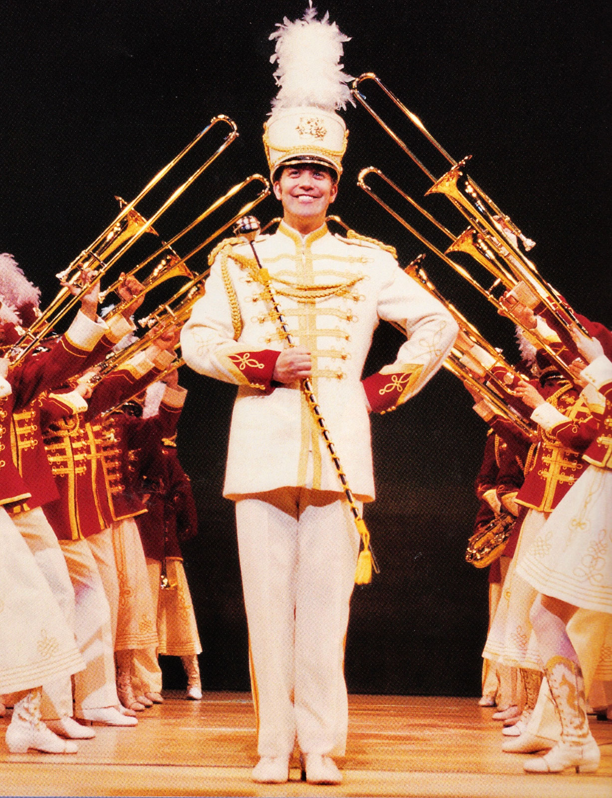 """Harold Hill (Craig Bierko)performing in the """"Finale Ultimo"""" framed by the ensemble playing trombones. Harold Hill is dressed appropriately in a drum major suit and the ensemble playing the trombone are dressed in a bright red band uniforms."""
