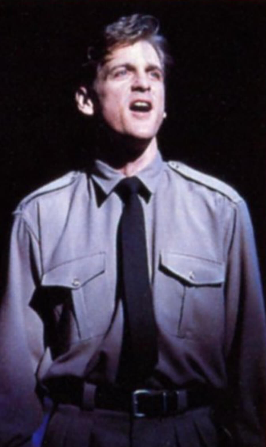 """Bill Kelly (Daniel McDonald in a military shirt and black tie) singing in a solo moment in the spotlight, singing """"The Last Girl""""."""