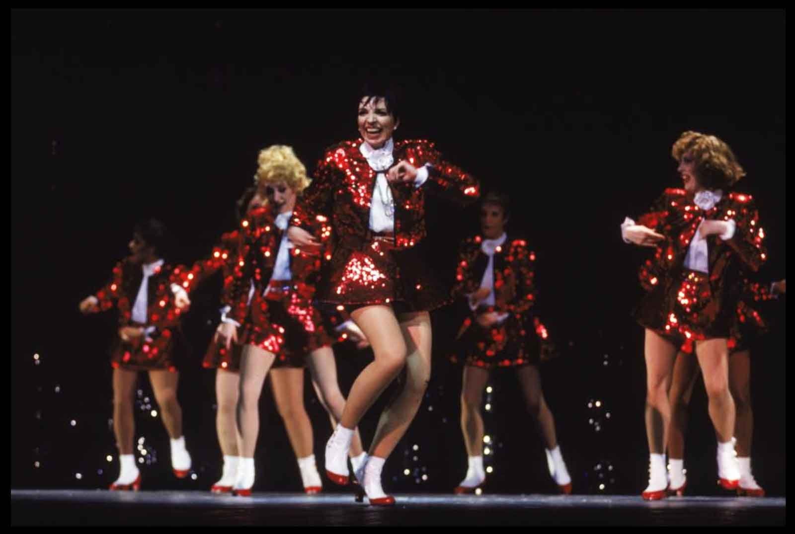 """Liza and her Demon Divas (all dressed in identical red sequin suits) performing """"Stepping Out""""."""