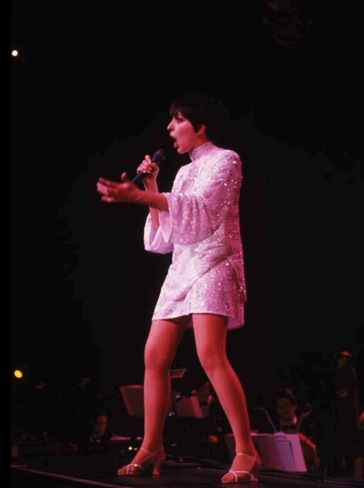 Liza in a solo moment, dressed in a white sequin dress, standing in second position and belting with a microphone and slight bend of the knees.