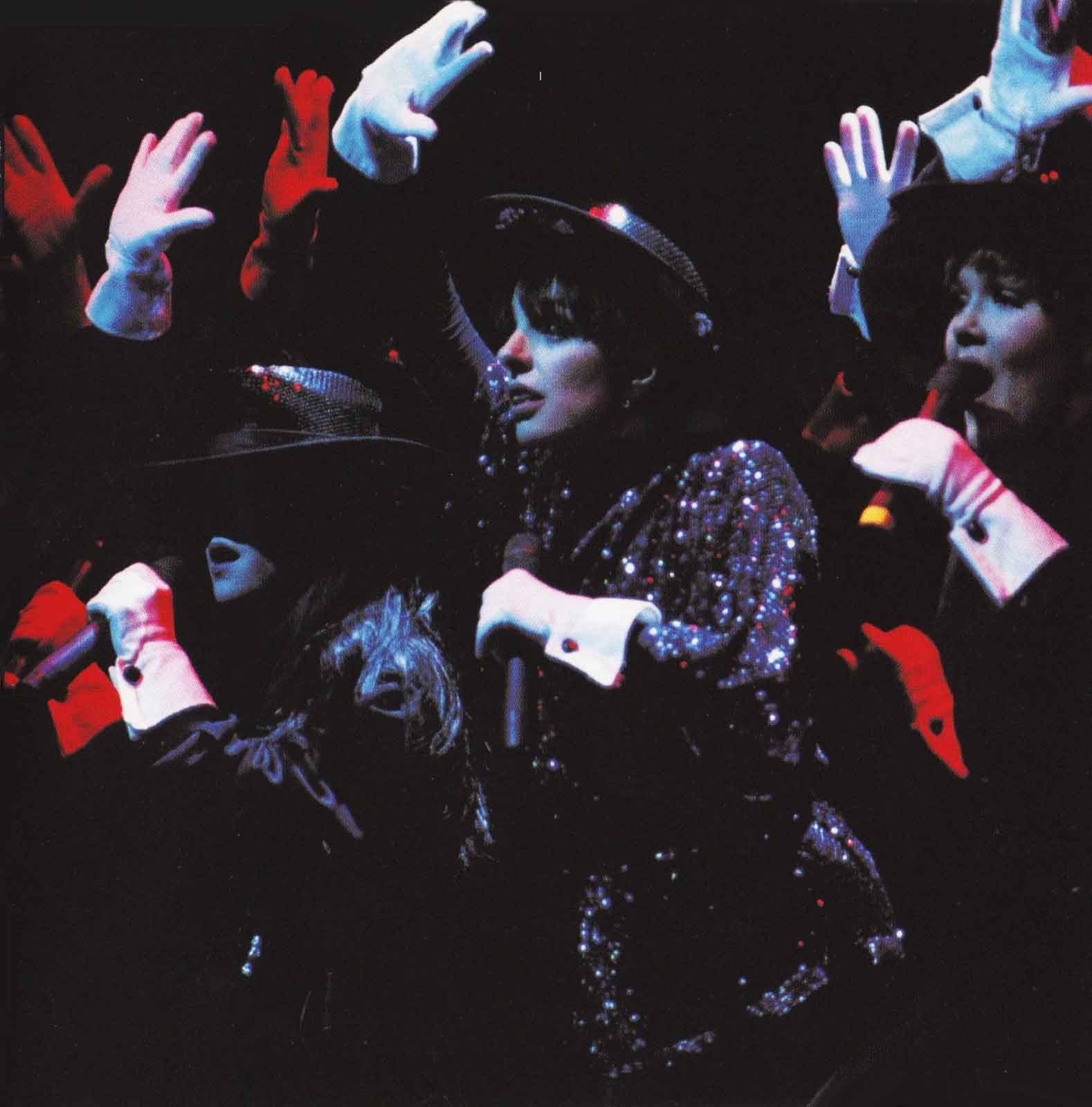 Liza and the Demon Divas, wearing white gloves and black sequined outfits.