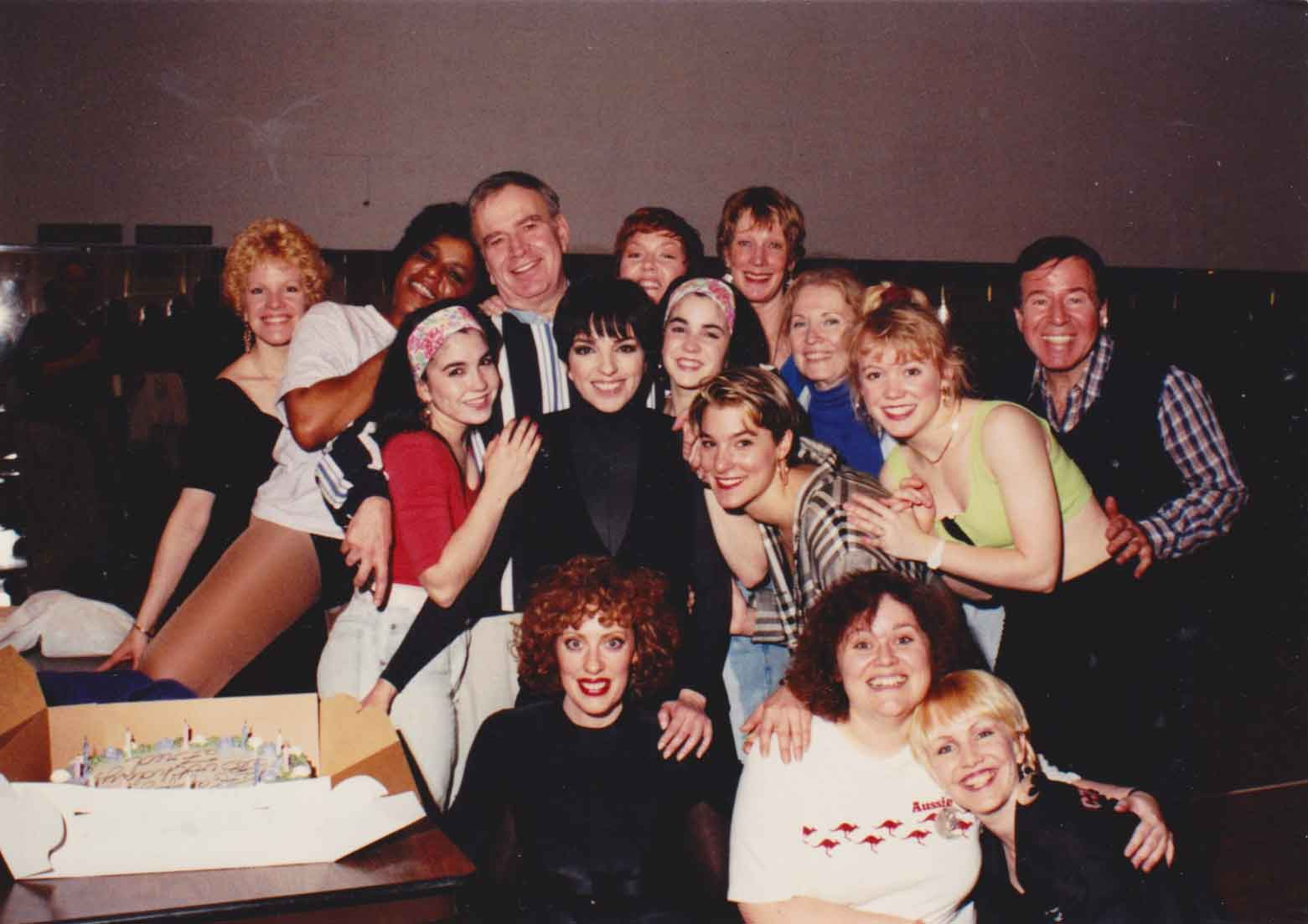 Liza, Stro, Fred Ebb, Peter Howard and the Demon Divas backstage at Radio City Music Hall. Everyone is hugging and there is a cake.