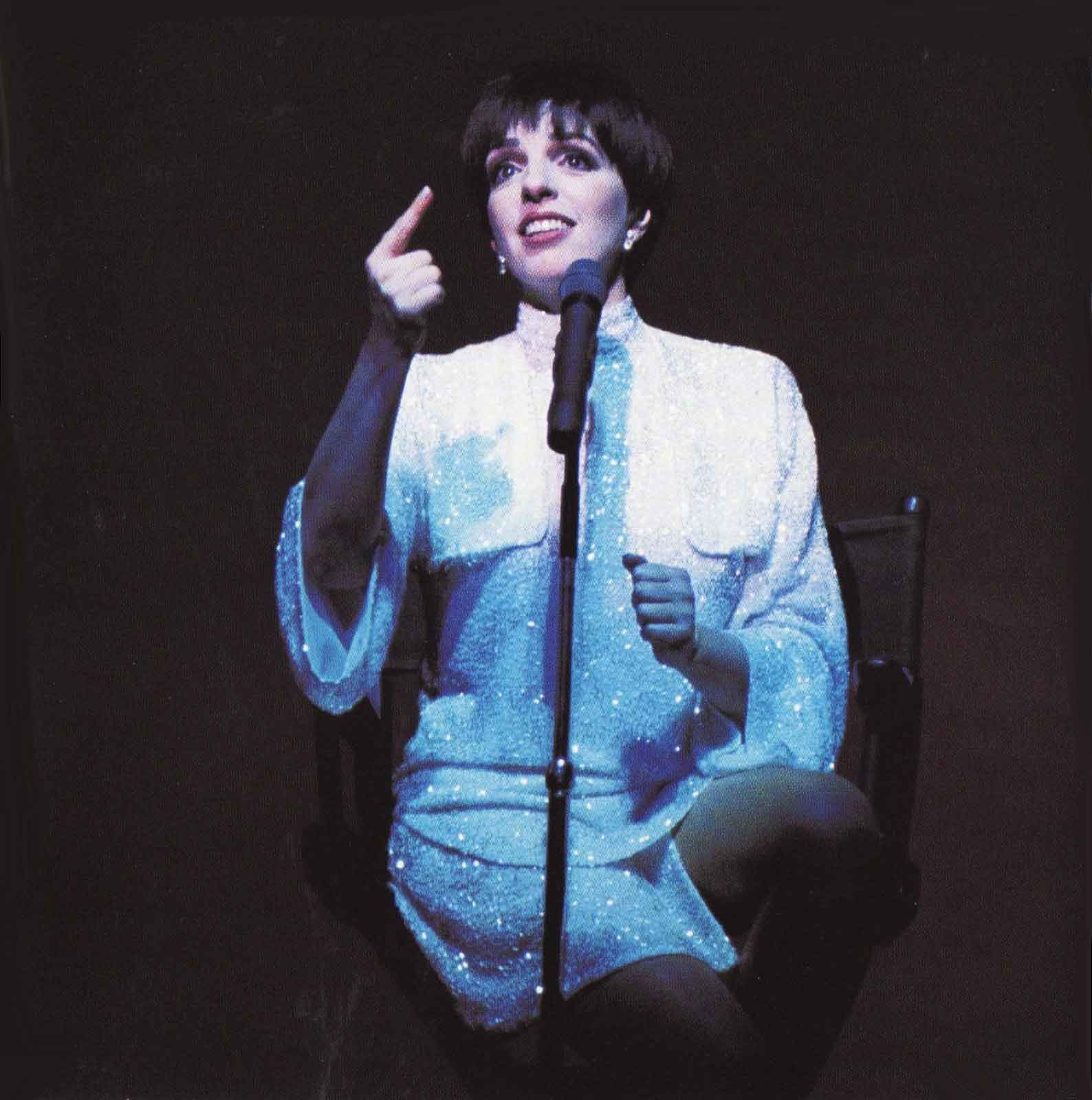 Liza Minnelli is seated on a stool in a white dress (with microphone stand in front of her) and pointing up.