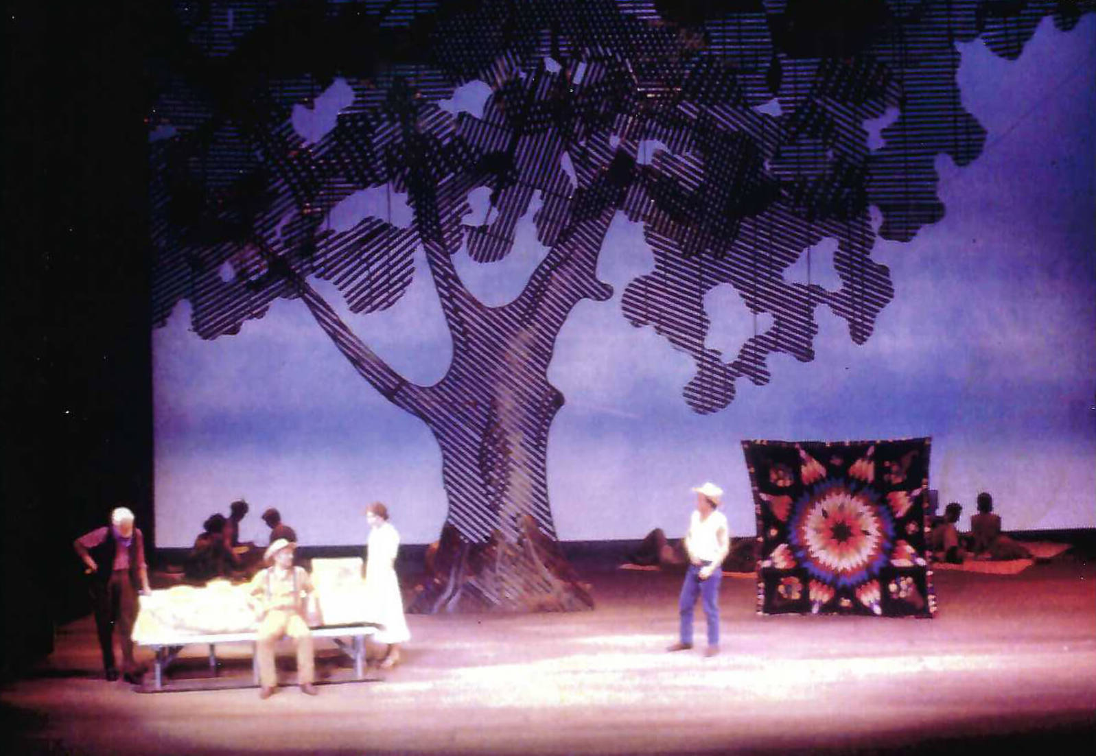 110 In the Shade at New York City Opera. Set by Michael Anania. Actors are under a large tree and there is also a quilt onstage.