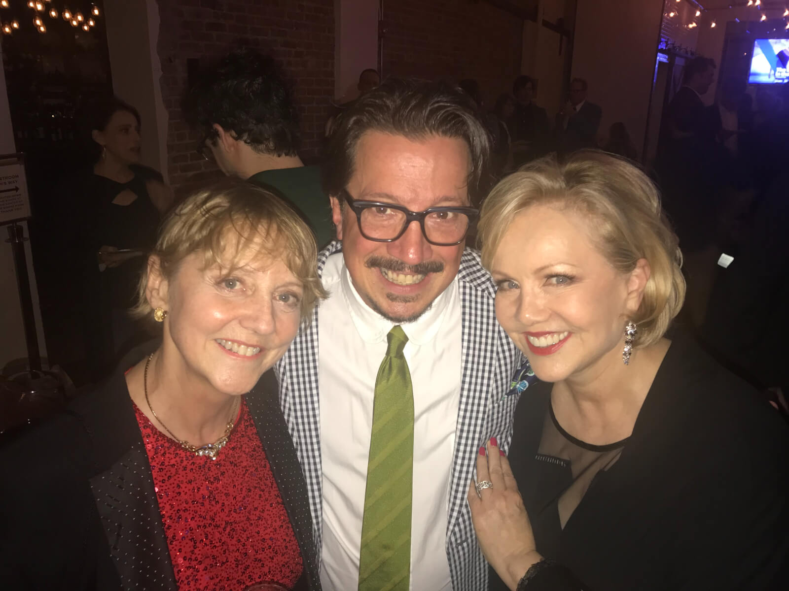 Associates Ginger Thatcher and Stacey Todd Holt with Director/Choreographer Susan Stroman. All are dressed elegantly: Ginger in red blouse, Stacey in green tie, and Stro in all blacks.