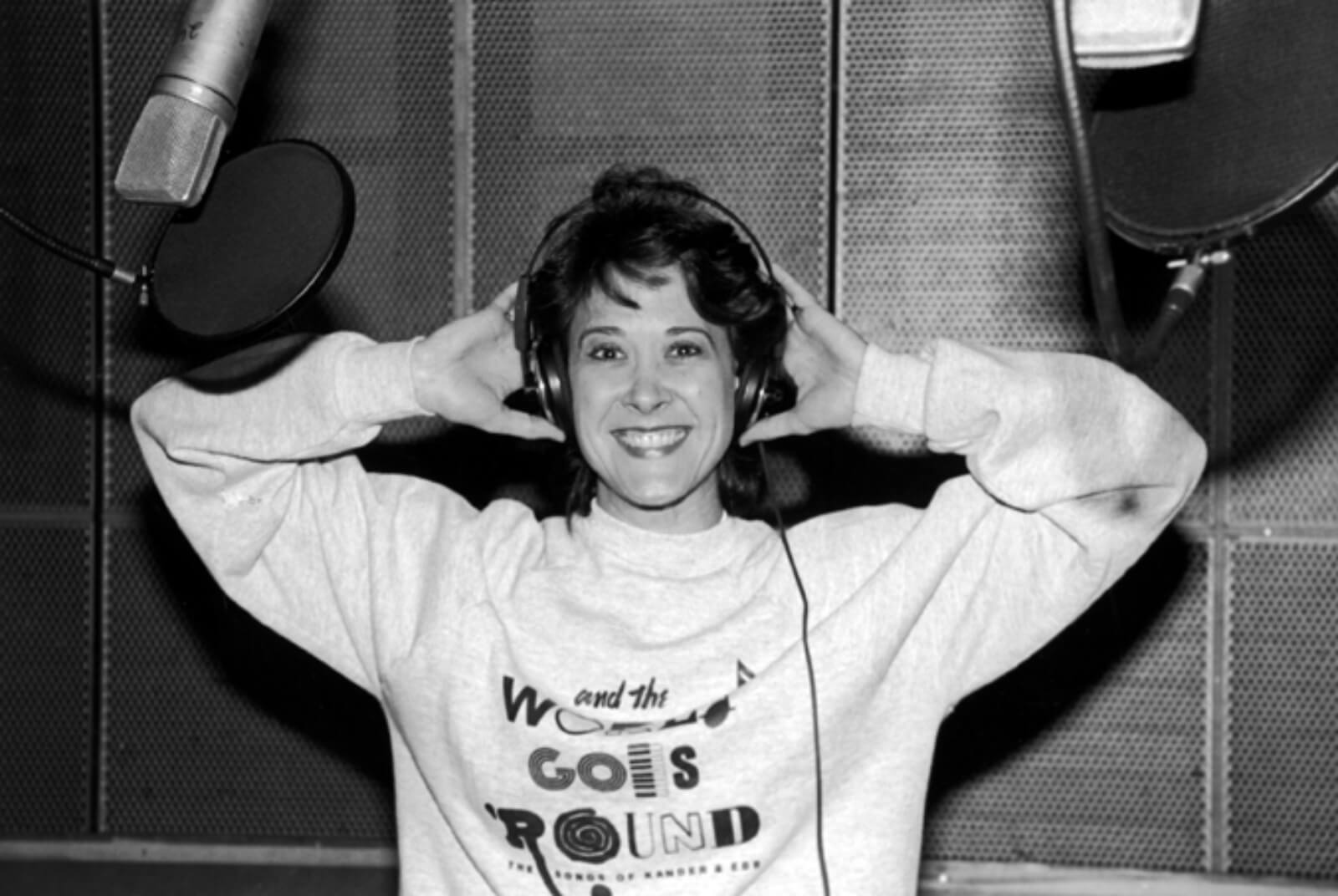 Black and white photo of Karen Ziemba recording the cast album to And the World Goes 'Round. She is wearing the show's logo on a sweatshirt and holding headphones.