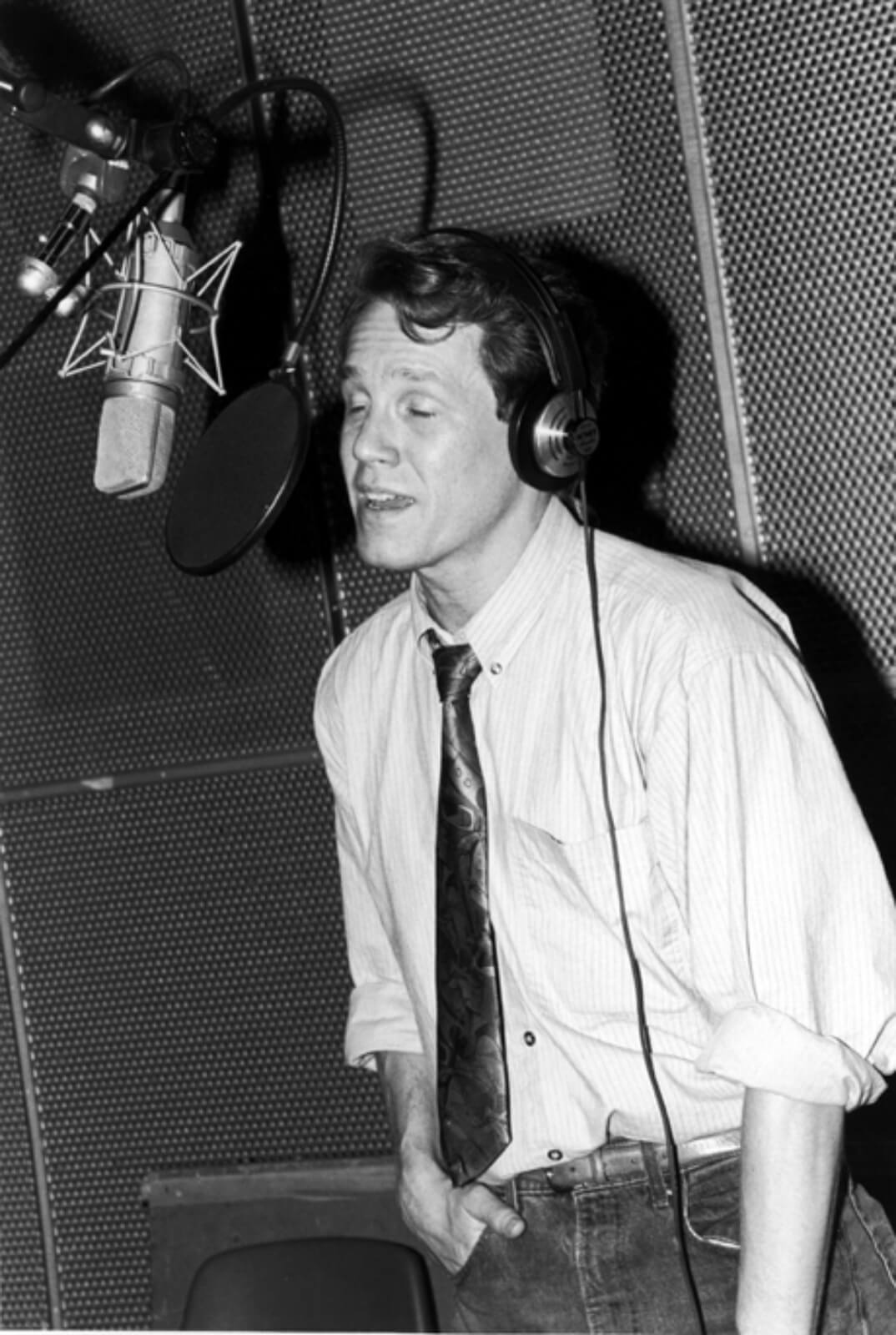 Black and white photo of Jimmy Walton recording the cast album to And the World Goes 'Round. He is standing in front of a microphone and wearing a tie.