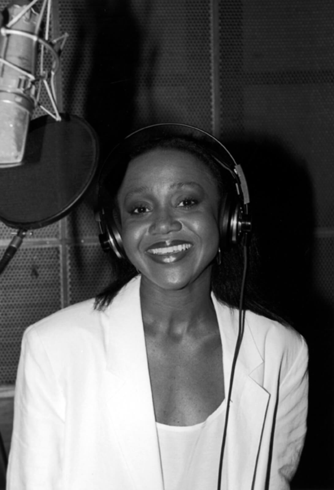 Black and white photo of Brenda Pressley recording the cast album to And the World Goes 'Round. She is dressed in all white and standing in front of a microphone.