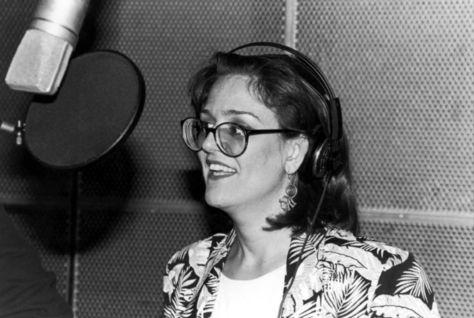 Black and white photo of Karen Mason recording the cast album to And the World Goes 'Round. She is wearing glasses and a blazer, standing in front of a microphone.