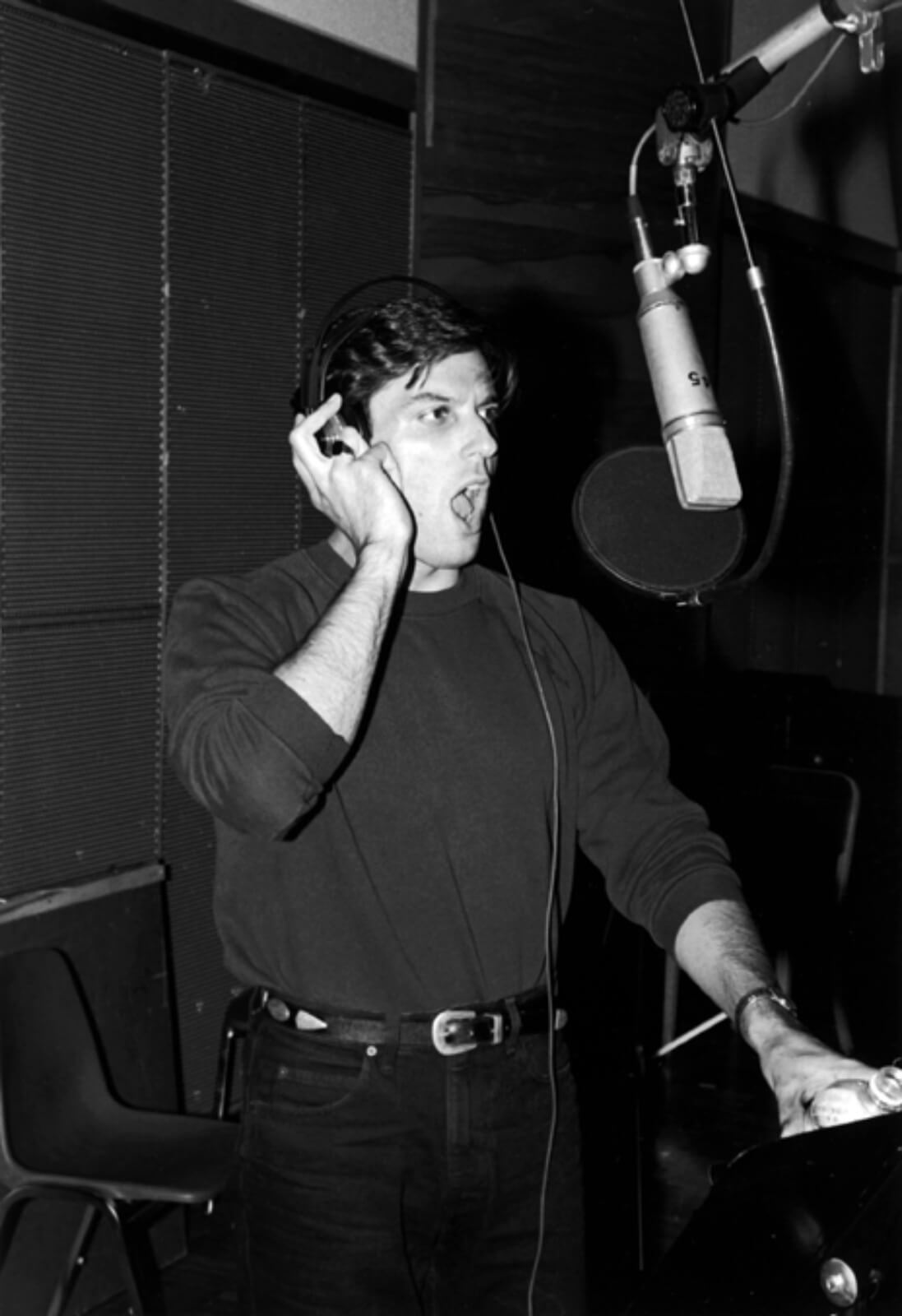 Black and white photo of Bob Cuccioli recording the cast album to And the World Goes 'Round. He is wearing a turtleneck and has one hand on headphones while singing into a microphone.