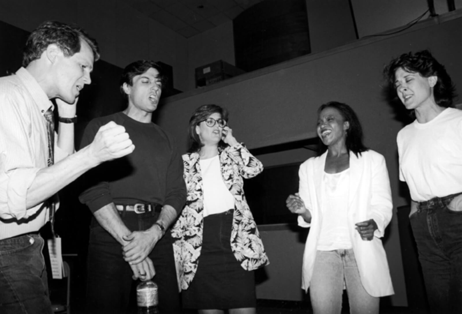 """Black and white photo of Jim Walton, Bob Cuccioli, Karen Mason, Brenda Pressley and Karen Ziemba recording """"Cabaret"""". They are standing in a circle: some with one hand to their ear or eyes closed."""