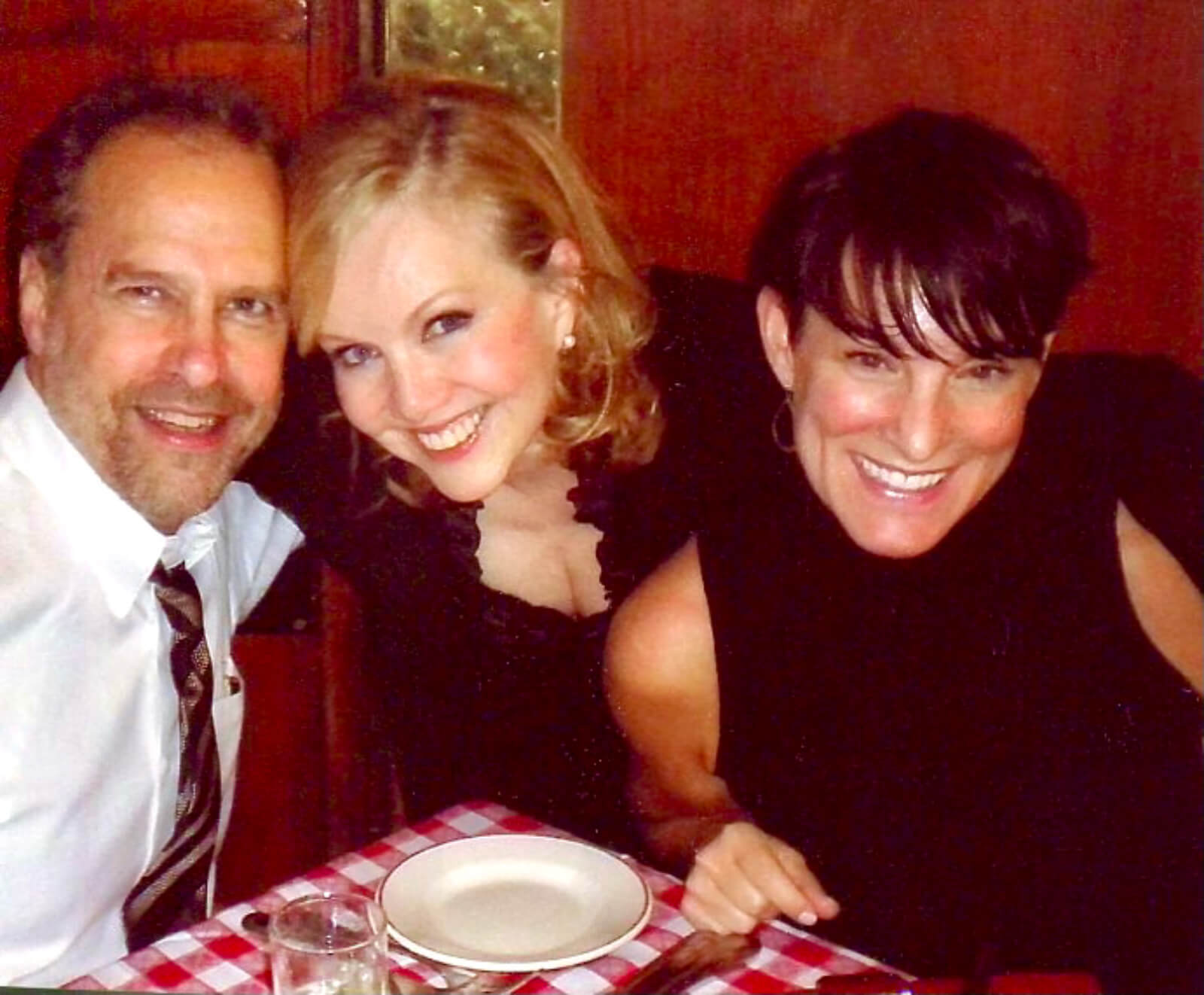 Stro's lawyer Rick Pappas and Resident Director/Associate Choreographer, Tara Young. All are seen eating in an Italian restaurant with a red checkered table cloth.