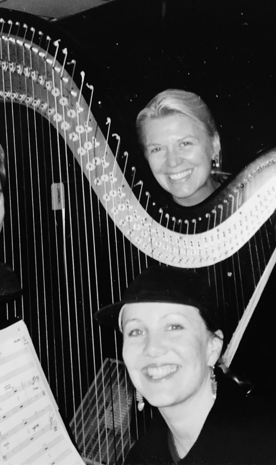 Black and white photo of Resident Director Niki Harris and Susan Stroman. They are backstage and standing with a large harp.