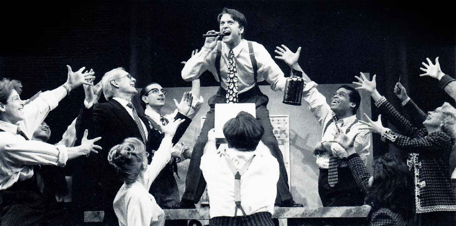 """Black and white photo of Josh (Daniel Jenkins) and the cast of Big The Musical singing """"Coffee Black"""". Daniel is on a desk and smoking a cigar."""