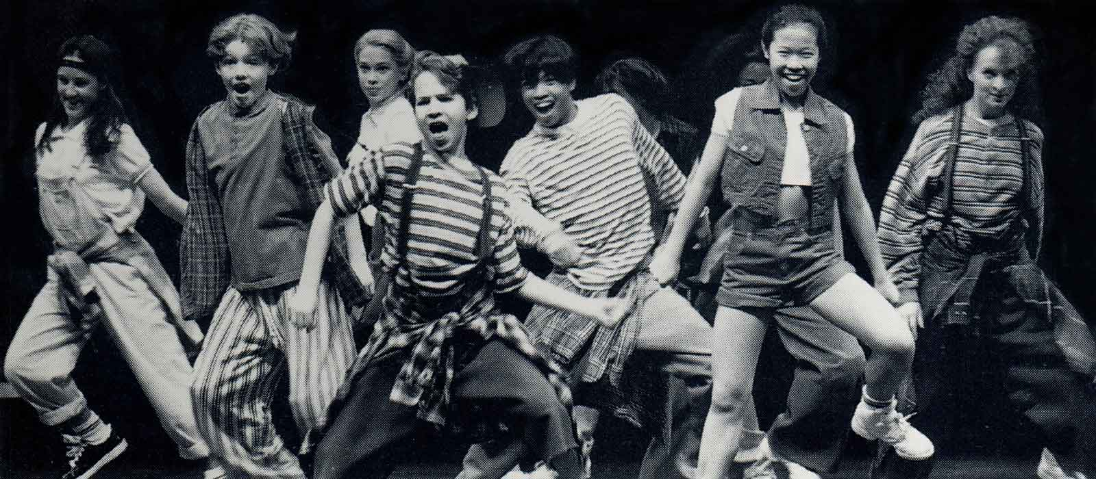 """Black and white photo of The Big Kids dancing to the the song """"Fun"""" in the Broadway company of Big The Musical. They are dressed as kids and in the midst of passionate movement: one leg is lifted and they are singing."""