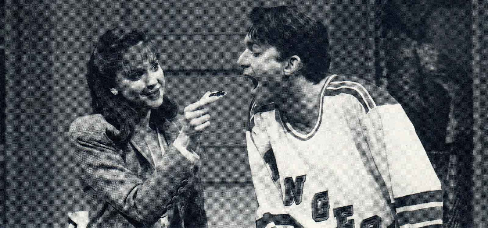 Black and white photo of Susan (Christa Moore) feeding caviar to Josh (Daniel Jenkins). He is dressed in a sports jersey and she is dressed in a business blazer.