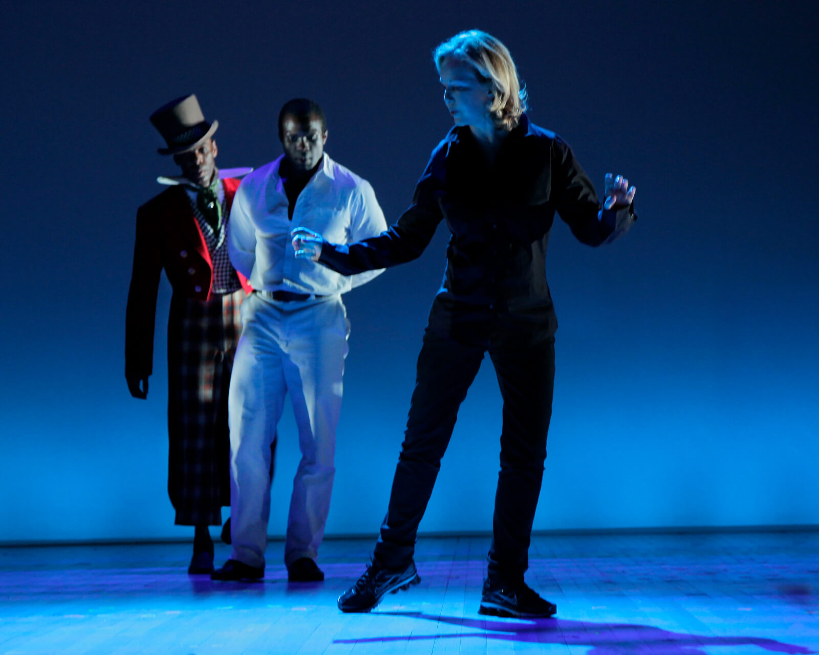 Stro onstage in blue lighting rehearsing The Scottsboro Boys with two actors in costume upstage watching.