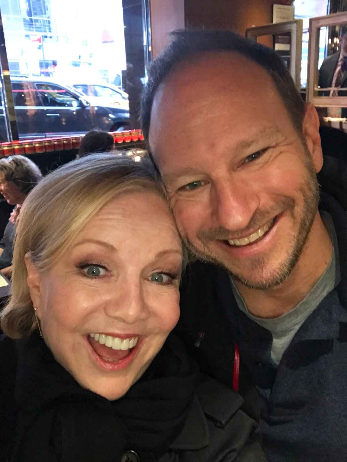 Director Susan Stroman and First AD Sam Hoffman on The Producers: The Movie Musical. They are both dressed in black and hugging with open mouth smiles.