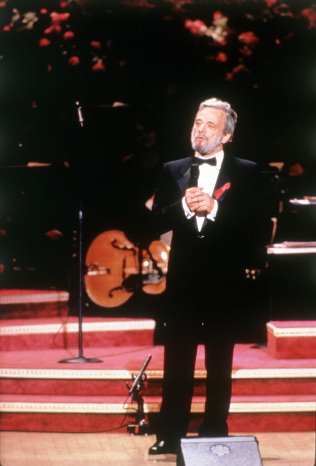 Stephen in a black tuxedo speaks to the audience.