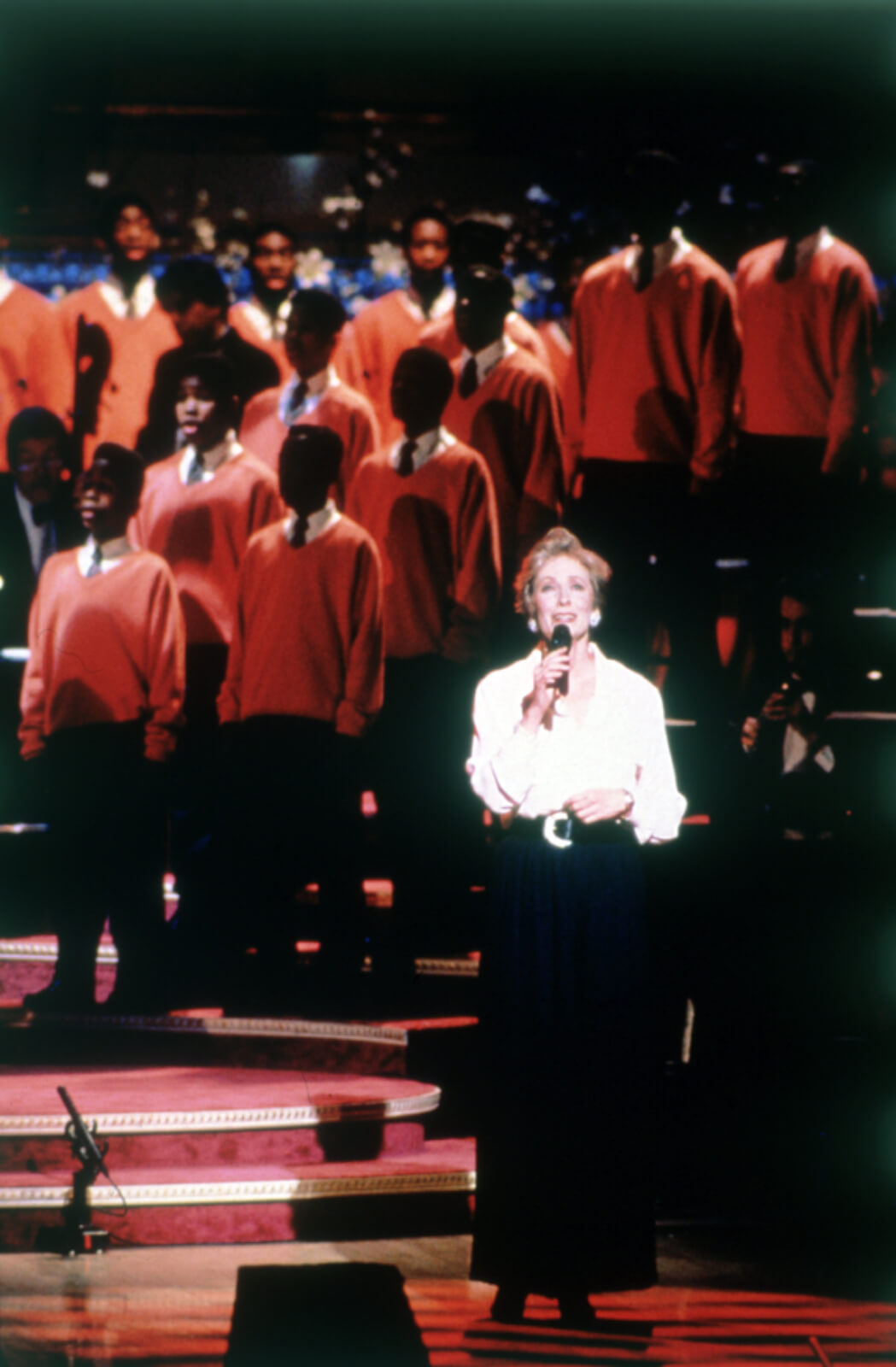 Betty Buckley, downstage and in a white blouse and black pants, and The Boys Choir Of Harlem. They are upstage in reddish orange robes and standing on risers.