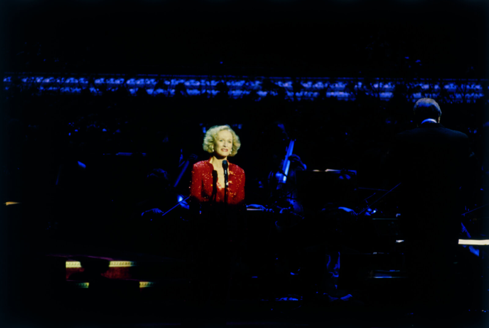 Glenn Close in a spotlight wearing red.