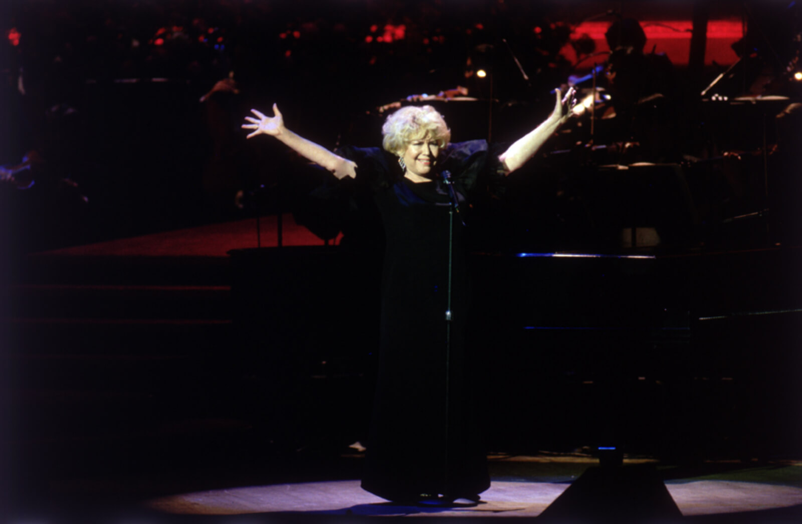 """Dorothy Loudon stands singing with both arms raised and open in a wide """"V"""""""