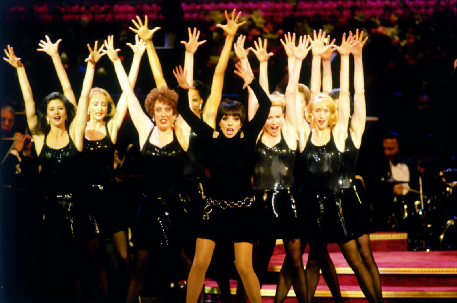 Liza Minnelli and her backup dancers in an all-black attire, dancing with arms up in the air.