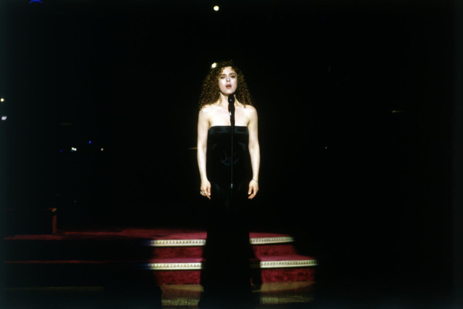 Bernadette Peters stands and sings. She is wearing a sleeveless long black dress.