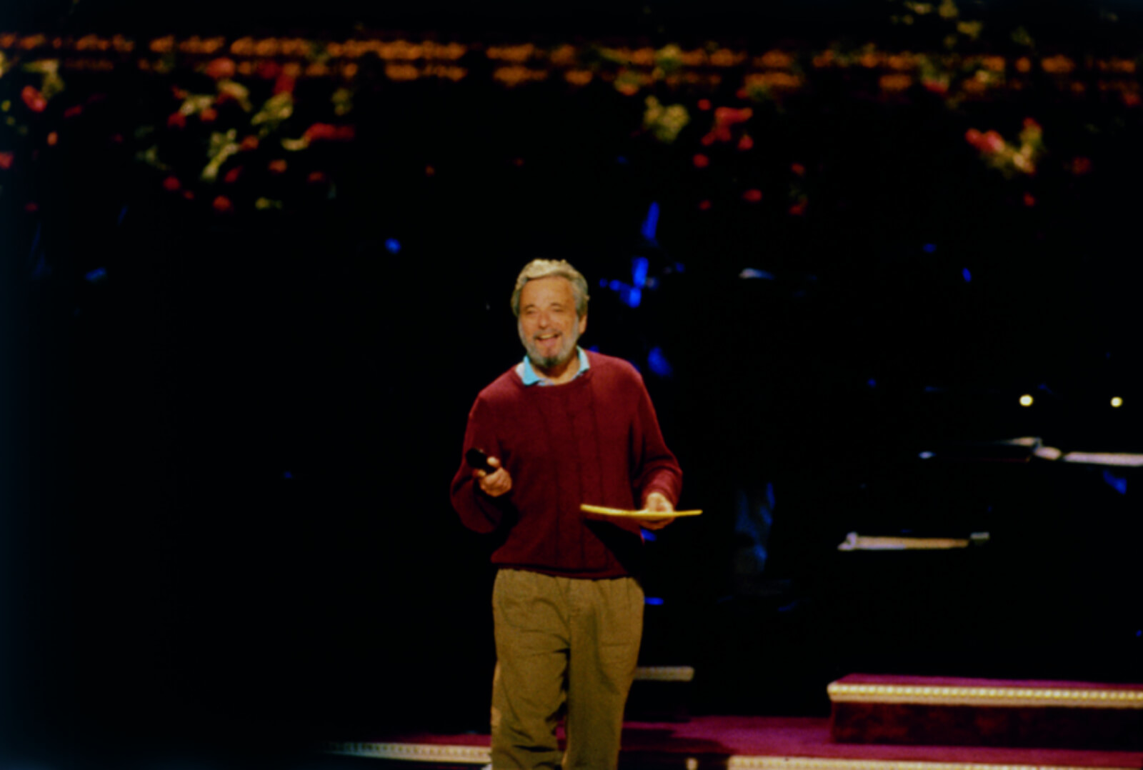 Stephen Sondheim in rehearsal. He is wearing a blue dress shirt and a maroon sweater, holding a microphone and notepad.