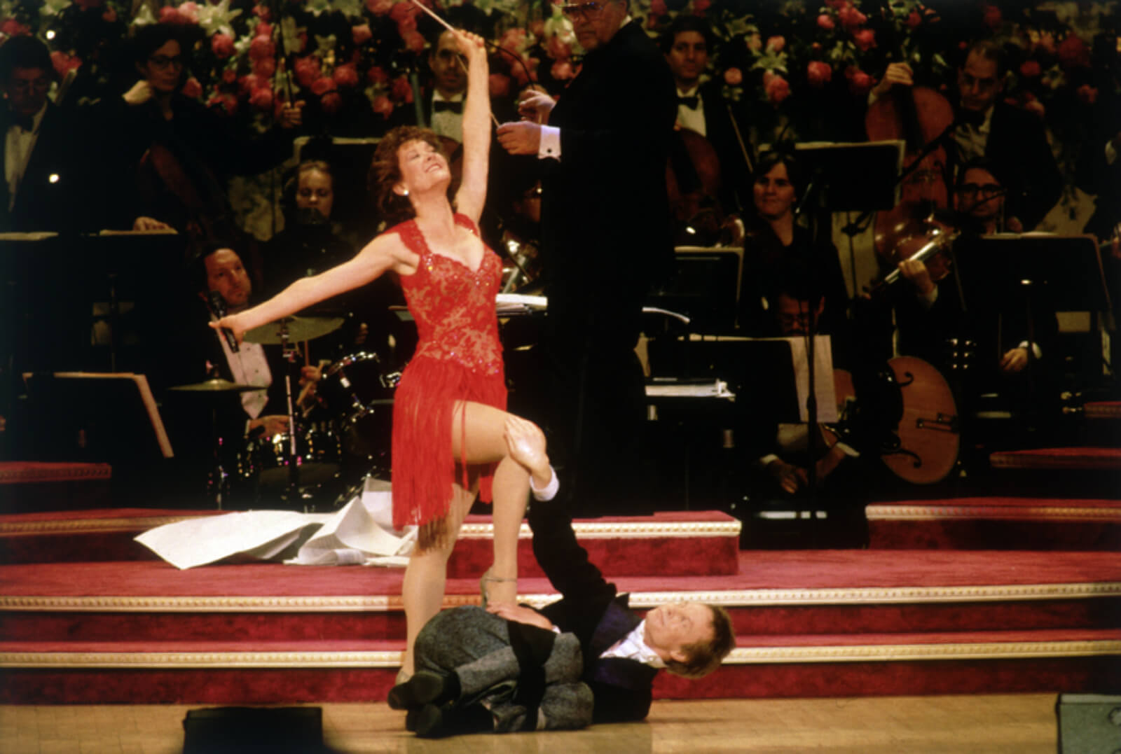 """Karen Ziemba and Bill Irwin performing """"Sooner or Later"""". She in standing over him in a red dress with one leg on him. He is laying in a cradle post on the ground in a suit."""