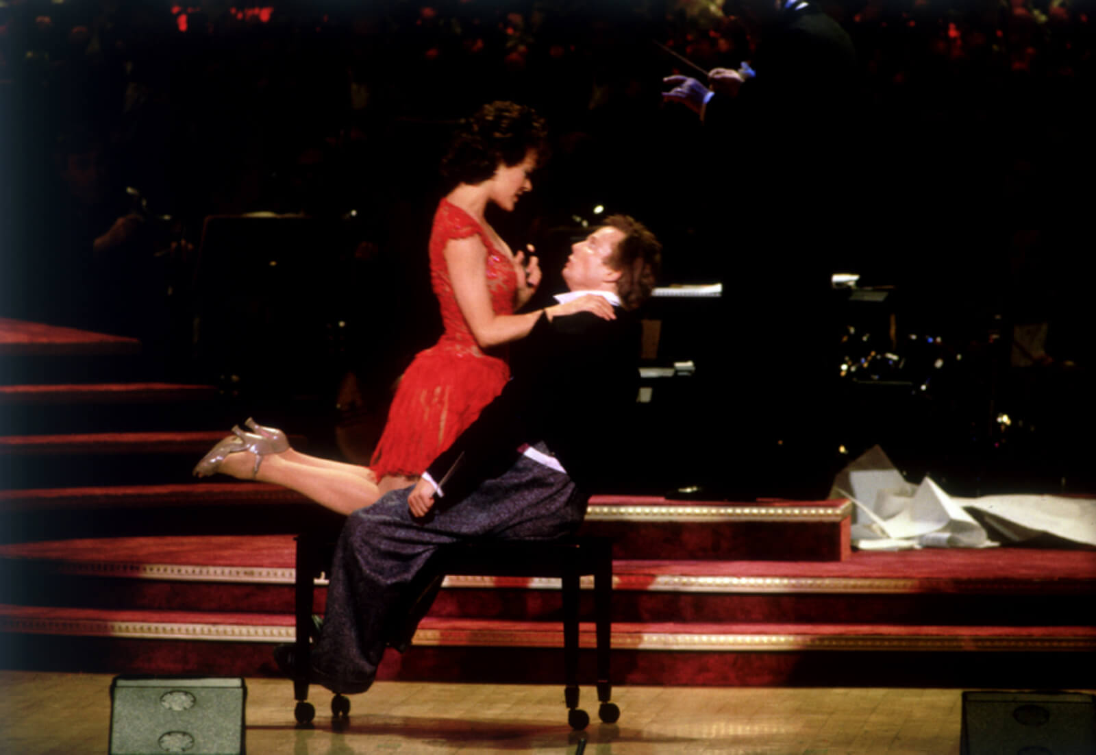 """Karen Ziemba and Bill Irwin performing """"Sooner or Later"""". He is seated on a chair and she is seated facing him. Both legs are bent in attitude position behind her."""