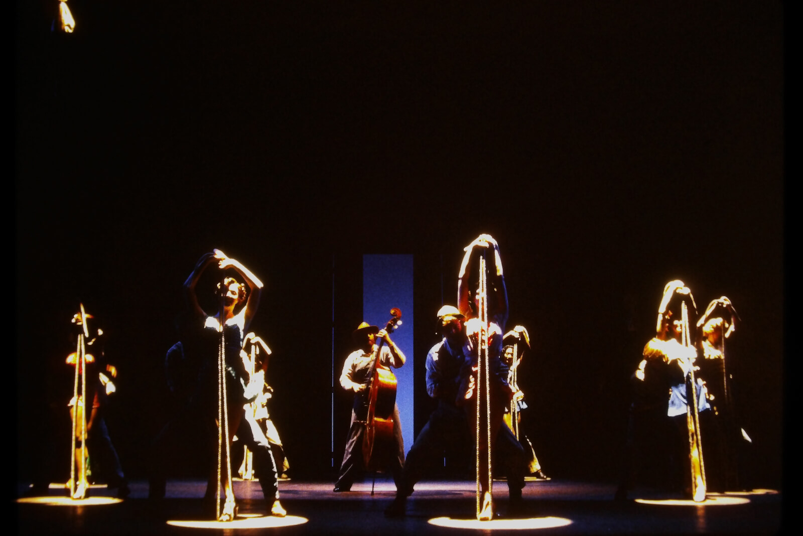 """Full Company of """"Slap That Bass"""" from the Original Broadway Production. 4 Women are standing over a folded rope while 4 men play the rope like a Bass: which is being played center stage. All are in sharp spotlights from above."""