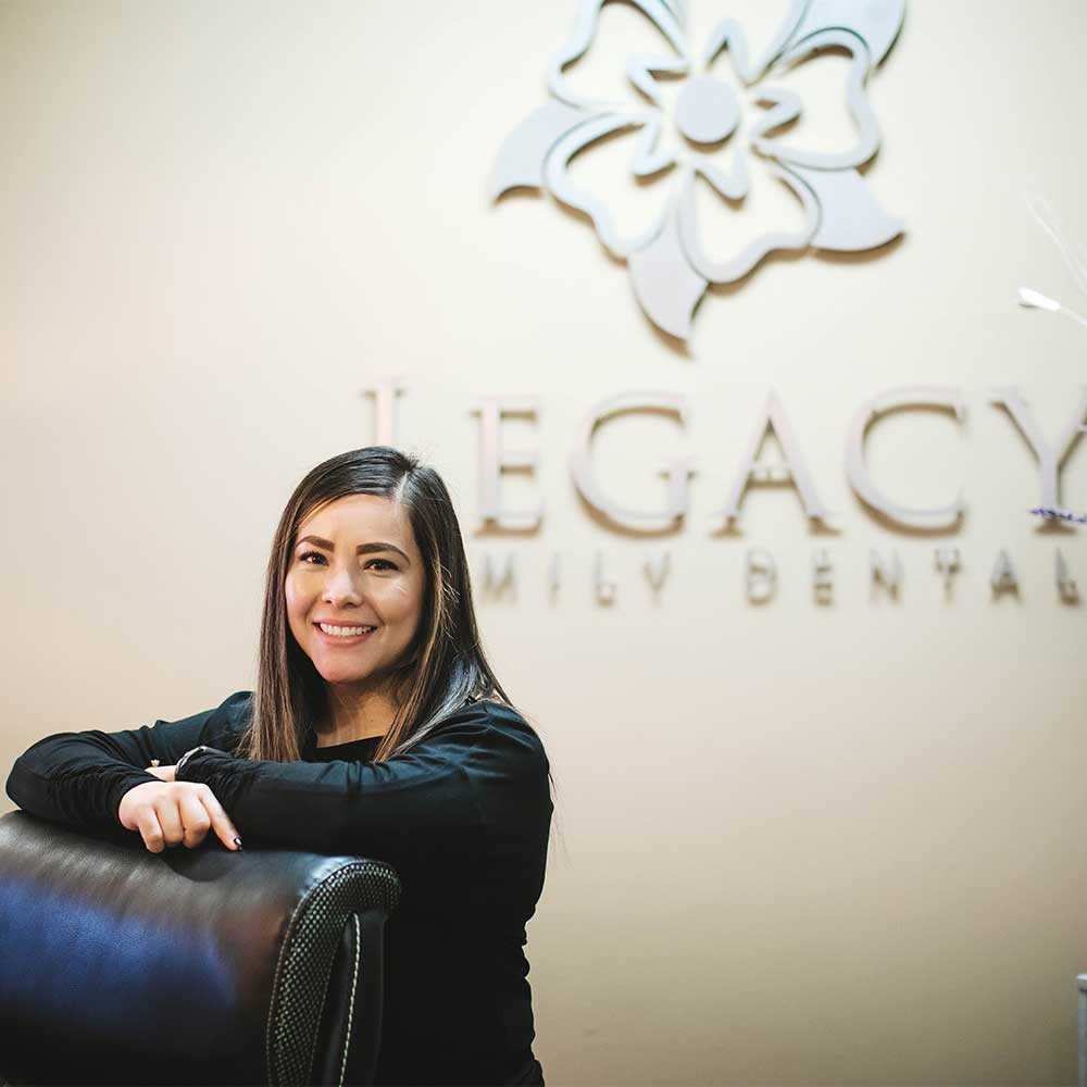 Photo of a smiling team member standing in front of a wall with the Legacy Family Dental logo