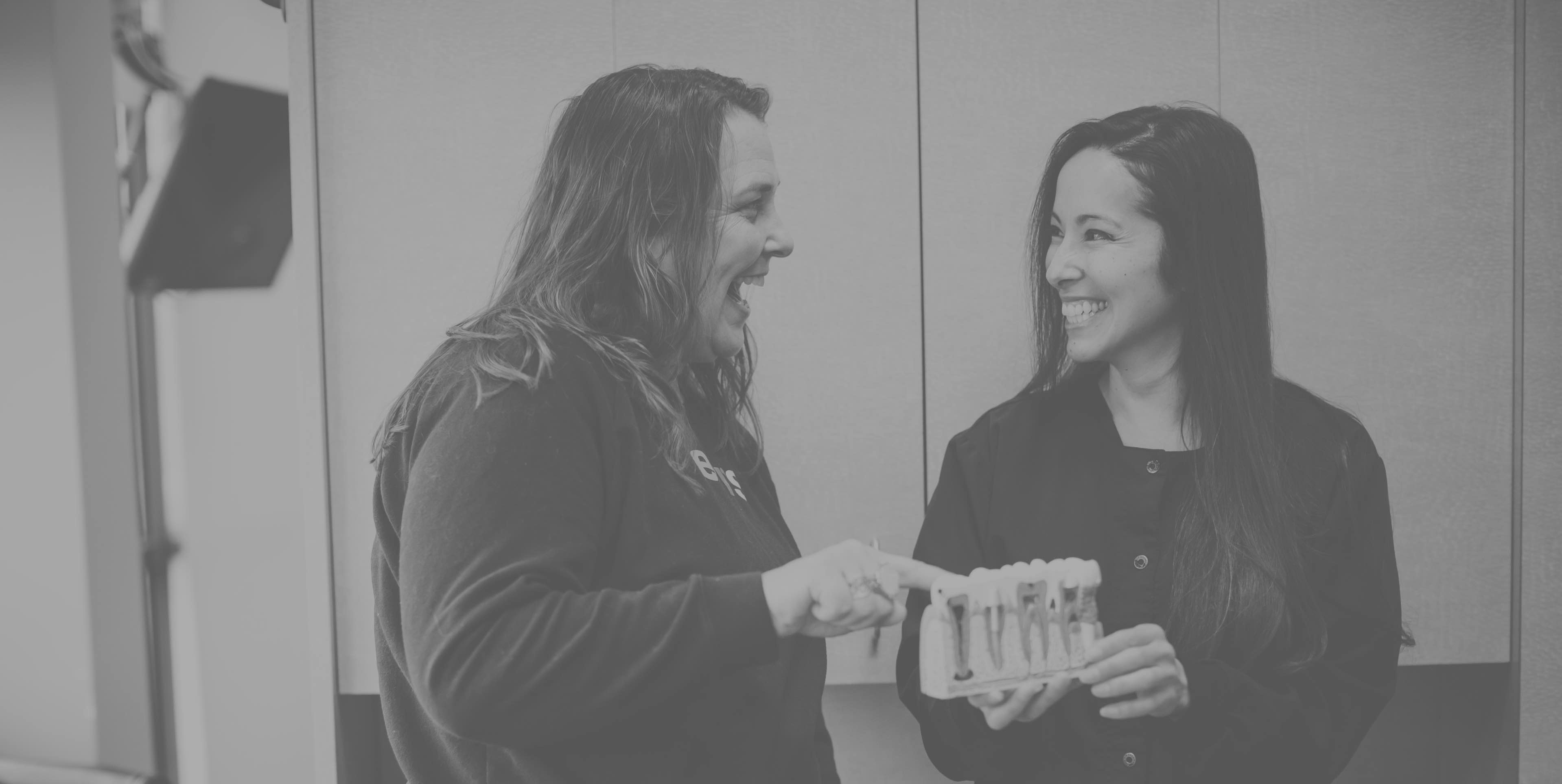 Photo of a team member and a patient looking at a dental implant model