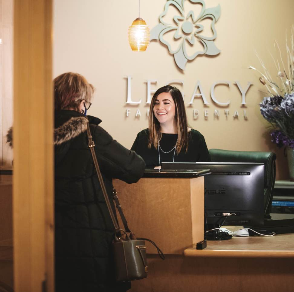 Photo of a smiling team member standing behind our front desk