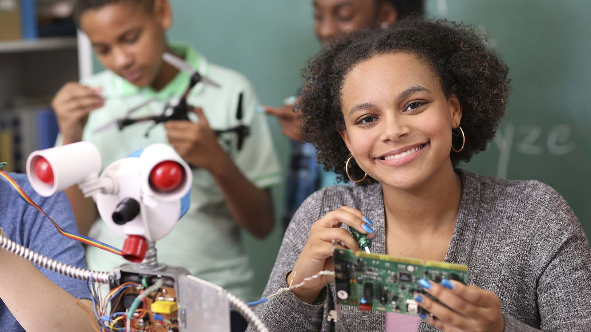 lady working on robotics with children in background