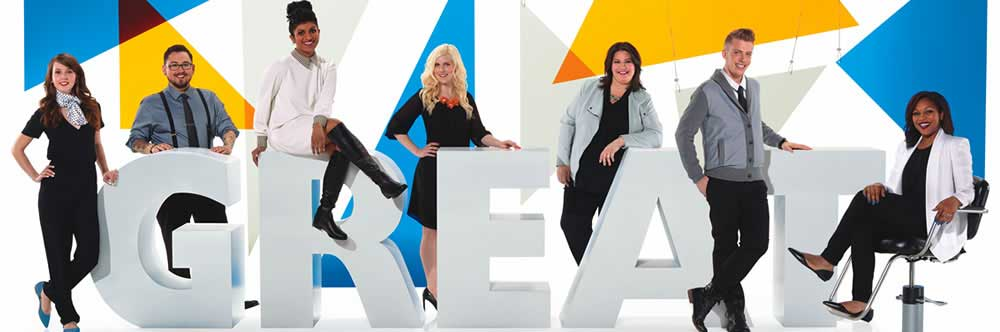 happy stylists, both male and female standing next to or sitting on large letters that spell GREAT