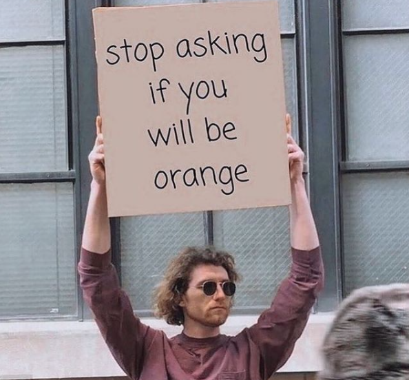 a guy holding a sign that says stop asking if you will be orange