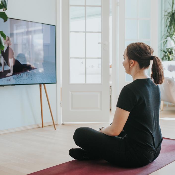 Unplugged blog over thuiswerken - Vrouw doet meditatie oefeninegn voor haar tv, close up