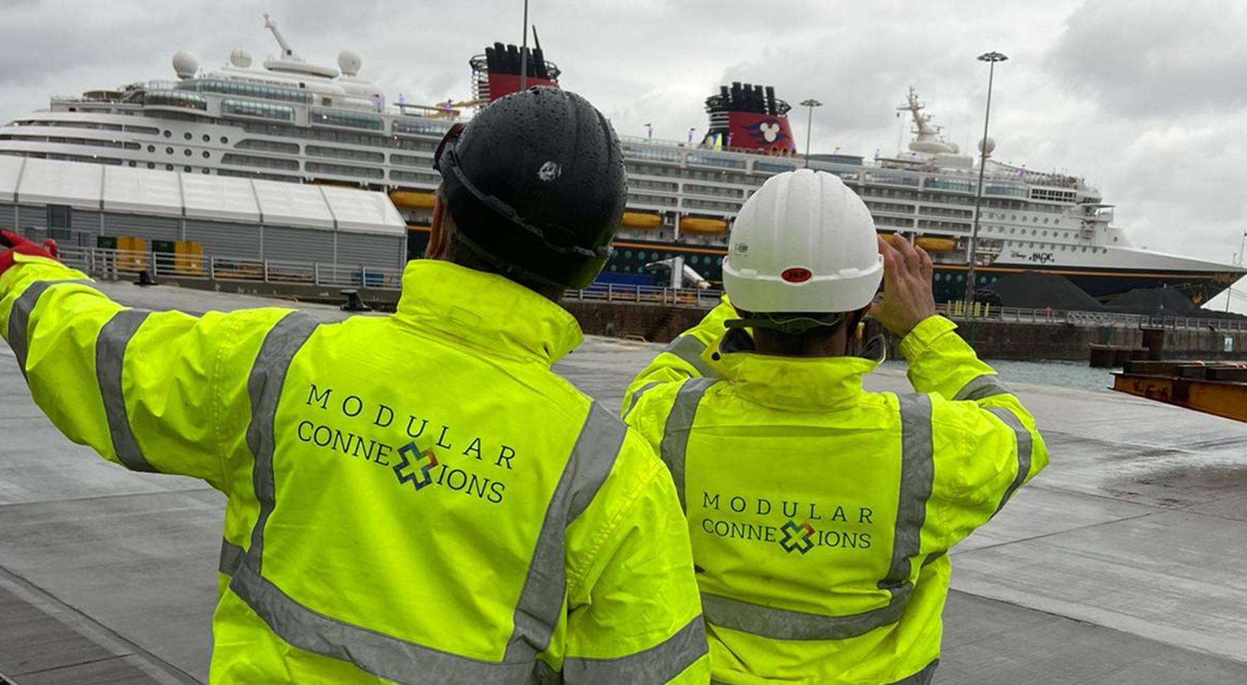Two Modular Connexions construction workers with yellow hi-vis jackets looking at a ship