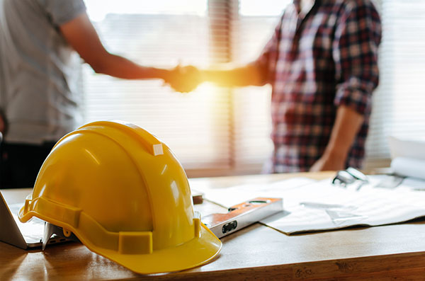 Yellow construction helmet and a spirit level on a desk with men shaking hands in background
