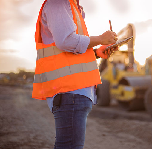 Construction worker onsite with orange hi-vis vest using a tablet and stylus pen, yellow digger in the background