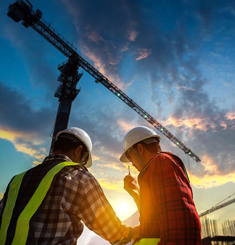 two construction workers onsite at sunset with crane above them