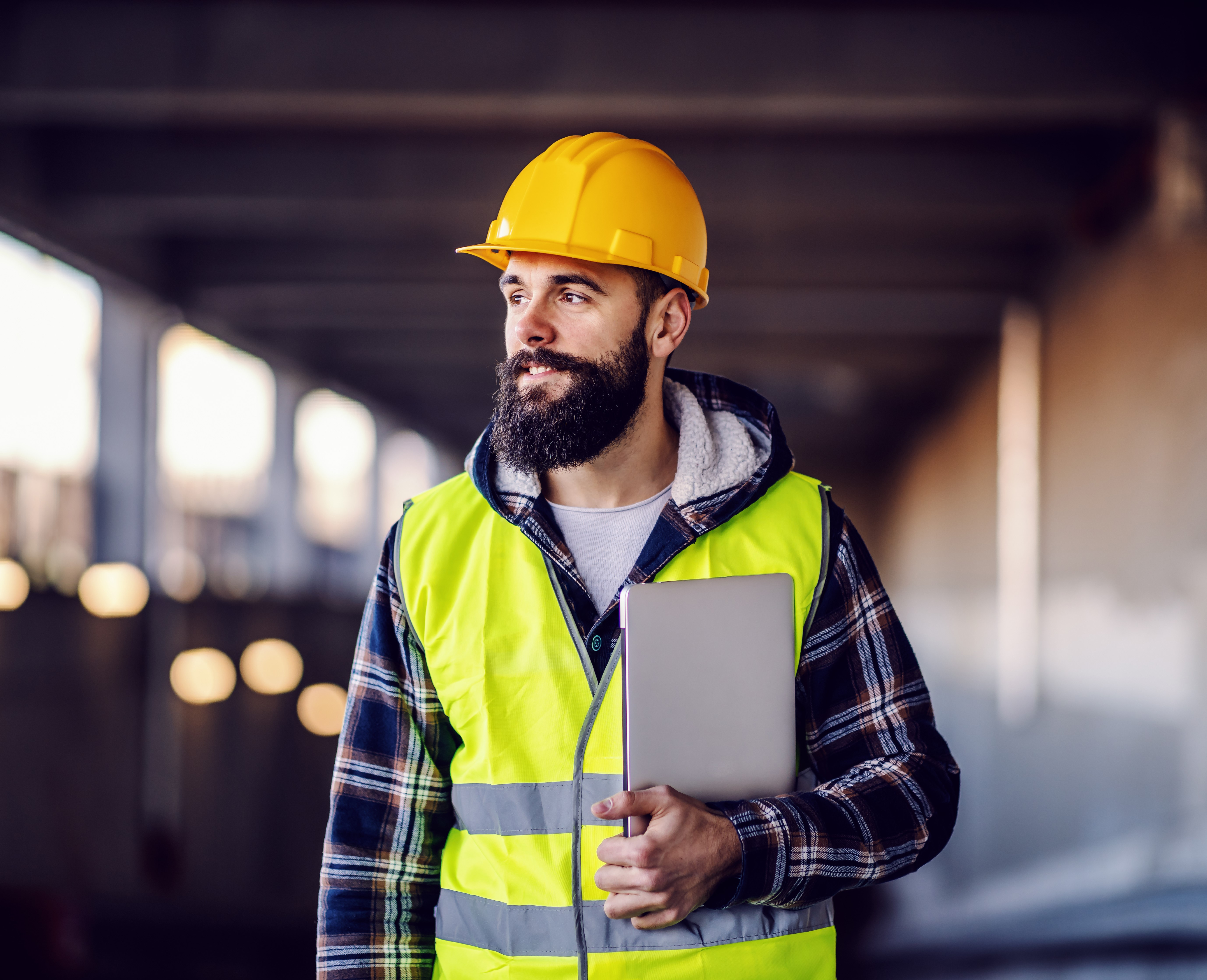 construction worker in high vis holding a tablet
